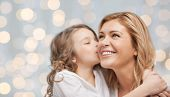 people, happiness, love, family and motherhood concept - happy daughter hugging and kissing her mother over holiday lights background