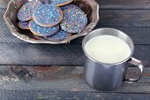 Glazed cookies in metal bowl and mug of milk on rustic wooden planks background