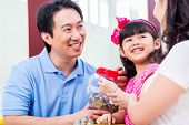 Chinese family saving money for college fund of child, putting coins in jar