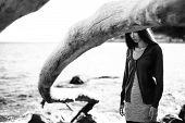 stock photo of dead plant  - Real young girl in casual clothes near the sea with dead tree over her head. black and white ** Note: Soft Focus at 100%, best at smaller sizes - JPG