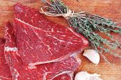 stock photo of flesh  - fresh raw beef meat fillet flesh with peppercorn and thyme ready to grill on wood figured old style board isolated over white background - JPG