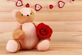Teddy bear with rose on wooden background, love concept