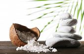 Still life of spa stones and coconut shell of sea salt on wooden surface with palm leaf isolated on white