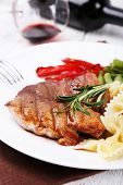 Steak with vegetables and pasta on plate on wooden plate