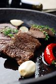 Steak in frying pan on table close up