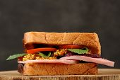 Sandwich With Ham, Beetroot, Mustard And Tomato On Black Background