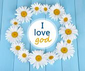 Chamomile wreath and text I love God on blue wooden background
