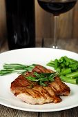 Steak with herbs on plate and bottle of wine on wooden table