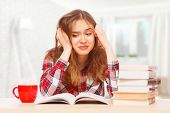Young girl stressed over her textbooks