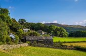 stock photo of hamlet  - Hamlet with stone barn and group of cottages surrounded by fields - JPG