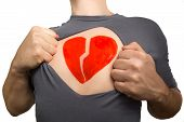 Man Tearing Apart Grey T-shirt. Broken Red Heart Painted On His Chest Isolated On White