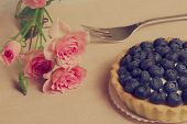 Tart with blueberry near roses