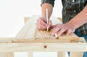 Cropped image of carpenter using measure tape to mark on wooden plank against white background