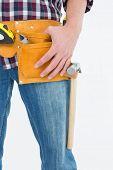 Cropped image of handyman wearing tool belt on white background