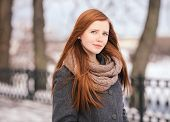Closeup portrait of cute redhead lady strolling in the park