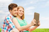 vacation, holidays, technology and love concept - smiling couple with tablet pc computer taking selfie over grass and blue sky background