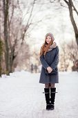 picture of redhead  - Winter full length portrait of a cute redhead lady in grey coat and scarf strolling in the park - JPG