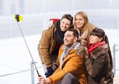 people, friendship, technology and leisure concept - happy friends taking picture with smartphone selfie stick on skating rink