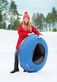 winter, leisure, sport, and people concept - happy teenage girl or woman with snow tube outdoors