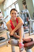 Portrait of brunette woman sitting on fitness bench