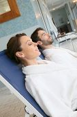 Couple relaxing in spa center longchairs