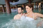 Couple enjoying bath in spa center jacuzzi