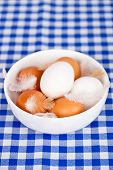 brown and white eggs,  feathers in a bowl on tablecloth background