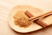 stock photo of cinnamon  - Three cinnamon sticks on a plank and cinnamon powder on a wooden spoon - JPG