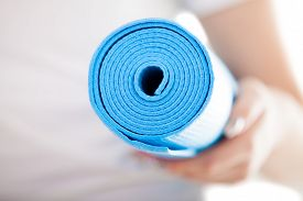foto of pilates  - Close up white woman hands holding folded blue yoga pilates mat for fitness training - JPG