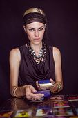 picture of fortune-teller  - Fortune teller forecasting the future with tarot cards on black background - JPG