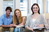 foto of psychologist  - Psychologist and happy couple smiling at camera in the office - JPG