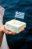 image of greek  - Holding in hand traditional greek feta cheese with greek flag on blue sea background - JPG