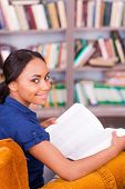 stock photo of toothless smile  - Top view of beautiful African female student holding a book and smiling while sitting at the chair in library - JPG