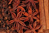 stock photo of cinnamon sticks  - Star anise cinnamon sticks and cloves on a wooden background - JPG