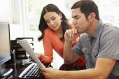 image of hispanic  - Hispanic couple working in home office - JPG