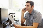 stock photo of hispanic  - Hispanic man working in home office - JPG