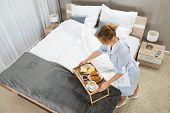 image of maids  - High Angle View Of Beautiful Maid With Breakfast Keeping On Table Tray In Hotel Room - JPG