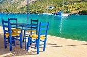 pic of greek  - Wooden blue chairs in Greek restaurant over sea bay with yachts in background - JPG