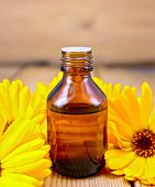 stock photo of marigold  - Dark bottle of aromatic oil, yellow marigold flowers on a background of wooden planks ** Note: Shallow depth of field - JPG