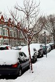 foto of slippery-roads  - Snow cityscape of a terraced street in London England with slippery blizzard conditions showing cars covered with ice and snow - JPG