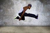 foto of parkour  - Black urban hip hop dancer jumping high on a concrete background - JPG