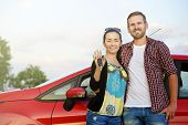 stock photo of key  - Portrait of happy attractive beautiful couple showingh the keys standing near the red car - JPG