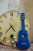 stock photo of ukulele  - Ukulele and classical clock at the wall - JPG