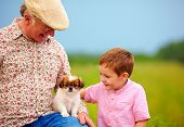 stock photo of grandpa  - grandpa and grandson playing with little puppy summer outdoors - JPG
