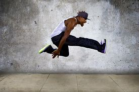 picture of parkour  - Black urban hip hop dancer jumping high on a concrete background - JPG