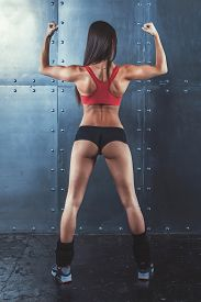 pic of shoulder muscle  - Muscular active athletic young woman showing muscles of the back shoulders and hands fitness - JPG