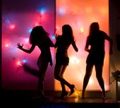 picture of night-club  - Dancing girls silhouettes in front of colorful disco lights