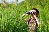 stock photo of boy scouts  - Young boy in a field looking through binoculars - JPG