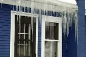 Ice hanging from the roof on a blue house