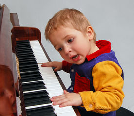 stock photo of children playing  - inspired little boy singing and playing piano - JPG